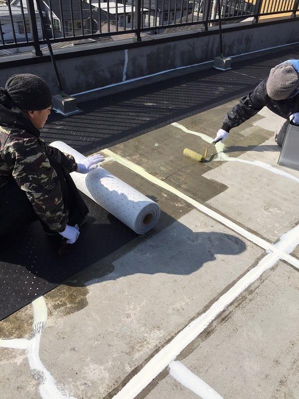 ボンドを塗りながら通気穴あきマットを敷く